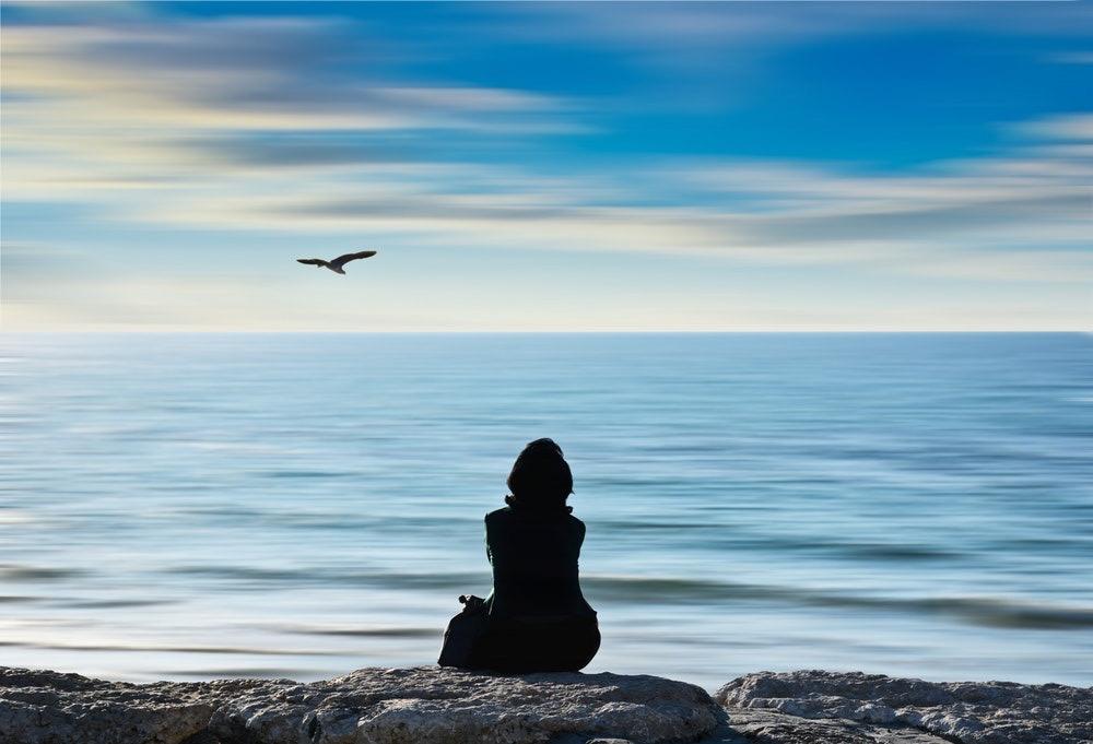 mujer de espaldas contemplando el mar